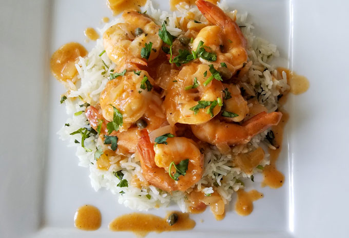 Cilantro lime rice as a bed for shrimp in a tomato caper sauce