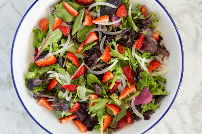 Partially assembled salad with greens, onions, and strawberry