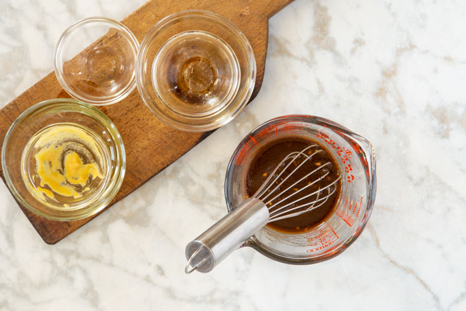 Balsamic dressing in a measuring cup and a whisk