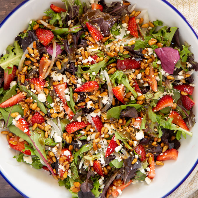 Feature image of a bowl of strawberry pine nut feta salad with balsamic dressing