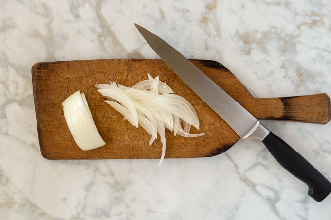 Thinly sliced onions on a cutting board with a knife