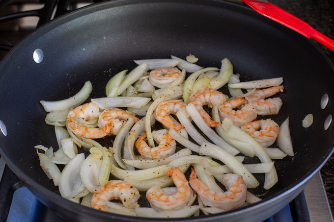 Sauteing the shrimp, onion, and garlic in half the olive oil