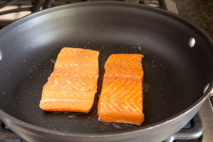 Raw seasoned salmon placed in the hot pan