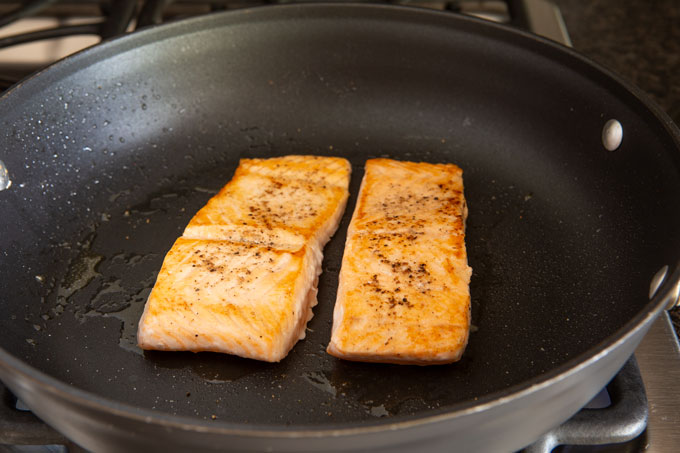 Seared salmon in a pan on the stove