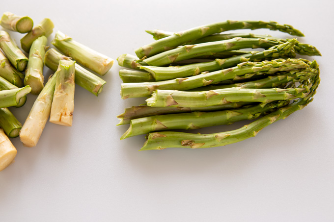 Raw asparagus spears with the ends broken off and separated