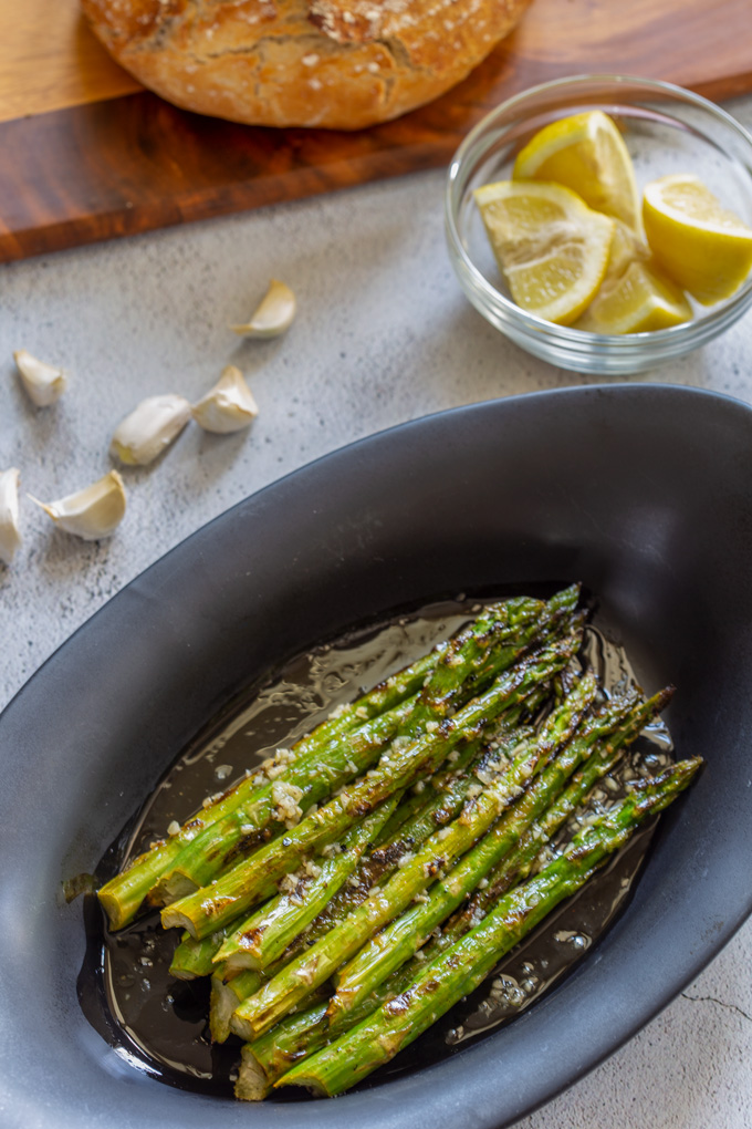 Grilled asparagus in a serving plate on a table with fresh bread, lemon and garlic cloves