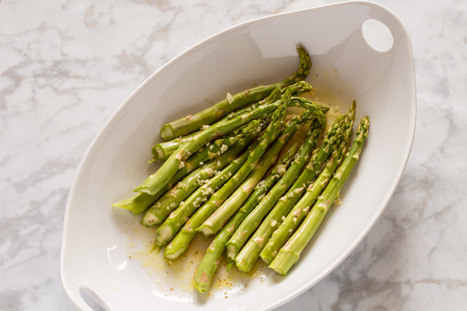 Raw asparagus marinating in a platter