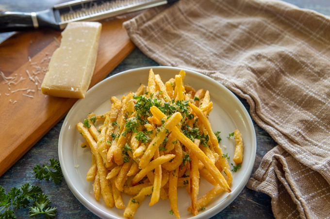 Landsacape image of plated pomme frites on a table with dish towel and Parmesan on a cutting board with a cheese grater