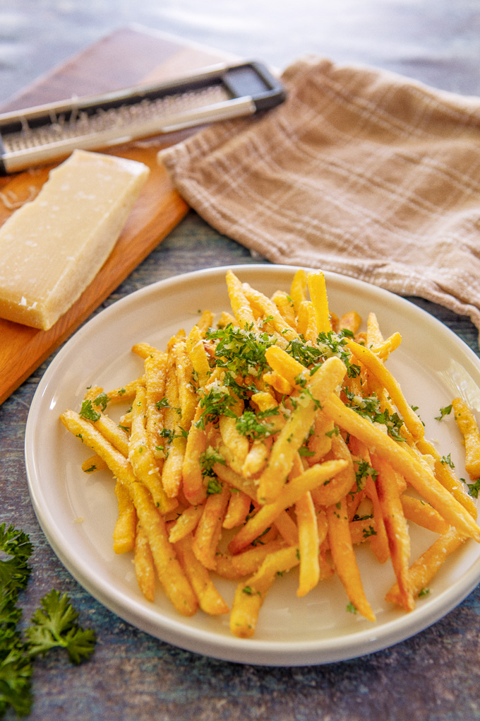 Portrait image of plated pomme frites on a table with dish towel and Parmesan on a cutting board with a cheese grater
