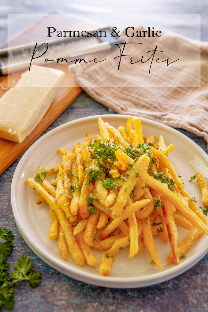Banner page with lable, on a portrait image of plated pomme frites on a table with dish towel and Parmesan on a cutting board with a cheese grater