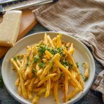 Feature image of plated pomme frites on a table with dish towel and Parmesan on a cutting board with a cheese grater