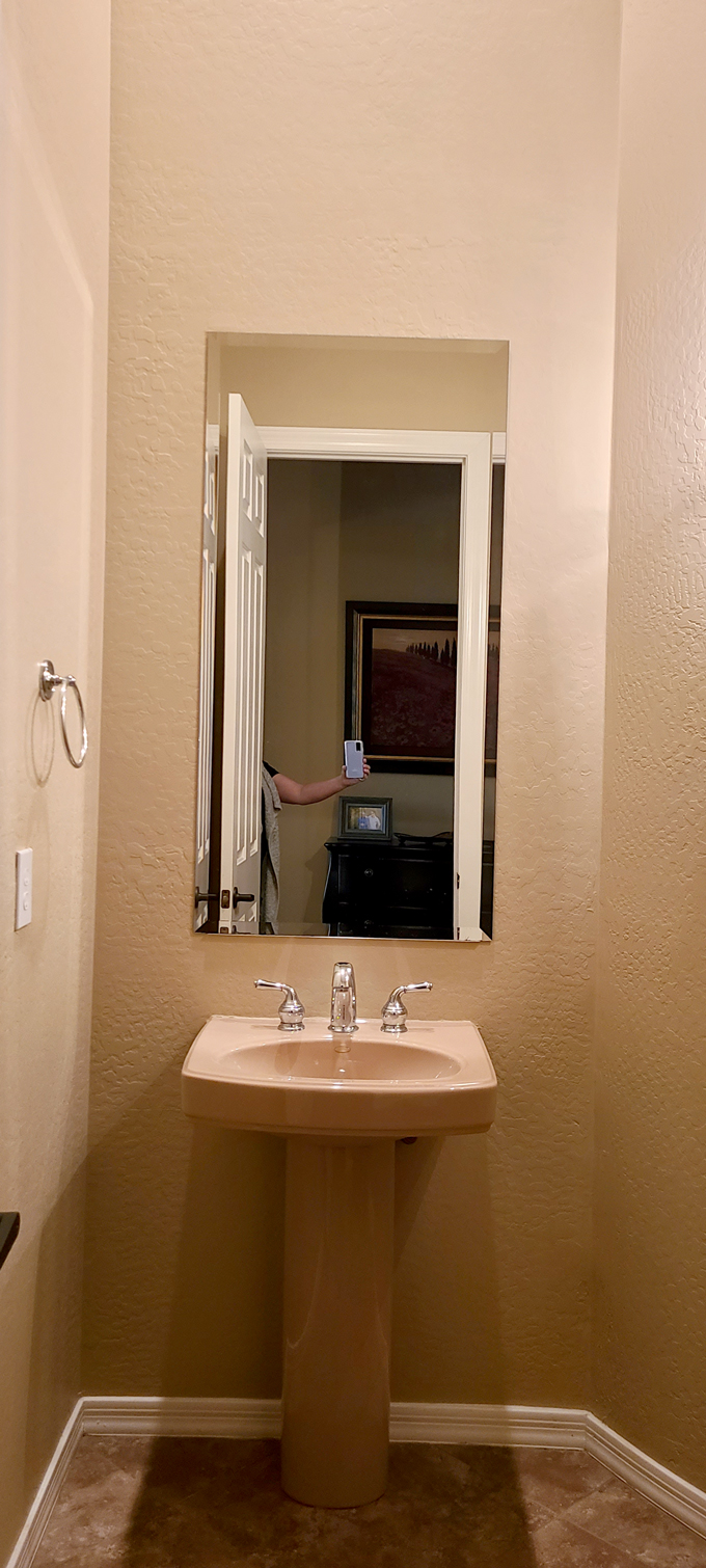 Half bath sink and mirror before the remodel
