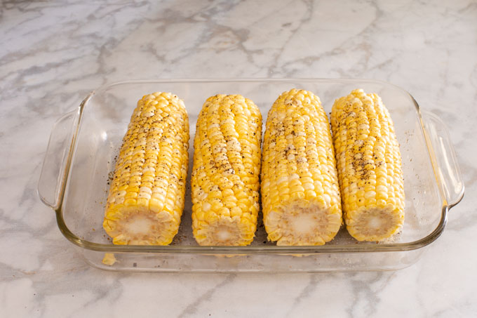 Ears of corn oiled, seasoned with salt and pepper, and ready to grill