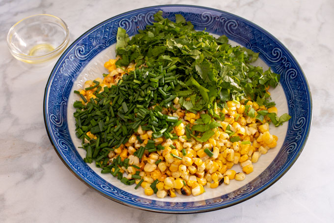 A bowl with the cut kernels, the chopped cilantro, and the chopped chives before the ingredients are tossed together