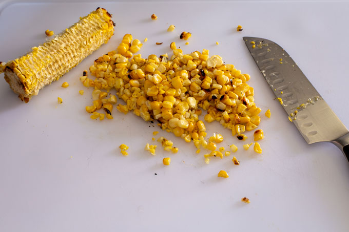 Image of aa grilled ear of corn on the cutting board with the kernels cut off the cob