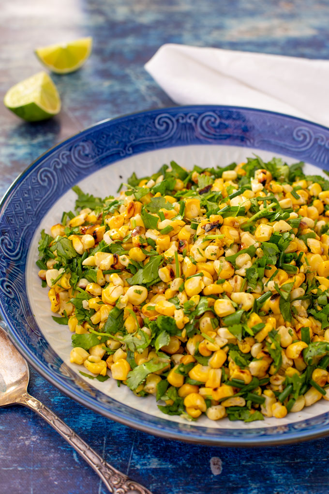 Grilled corn with cilantro and chives side dish in a blue bowl, ready to serve. Portrait orientation.