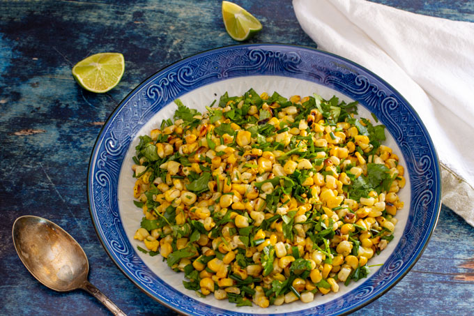 Grilled corn with cilantro and chives side dish in a blue bowl, ready to serve. Landscape orientation.