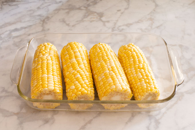 Ears of corn oiled and sitting in a glass dish