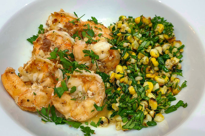 Garlic lemon shrimps with a side of grilled corn with cilantro and chives on the side