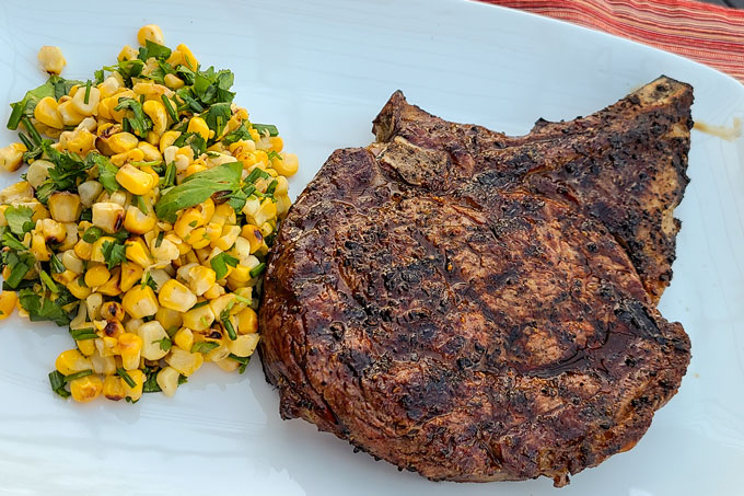 Grilled ribeye on a plate with the grilled corn with cilantro and chives on the side
