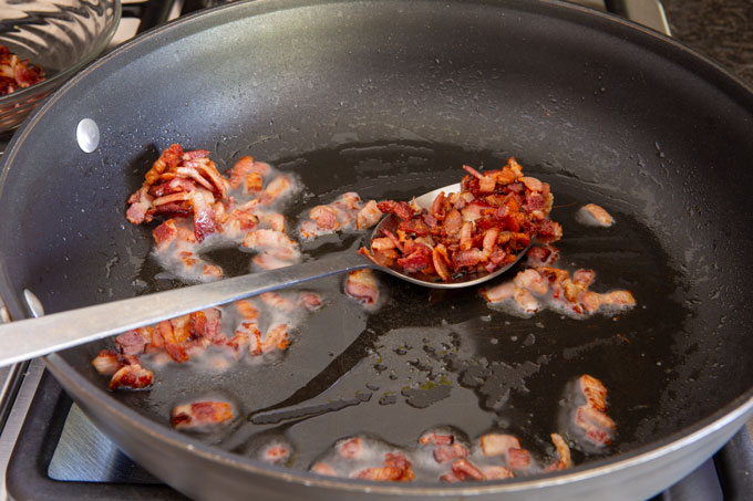 Crisping the bacon in a skillet.