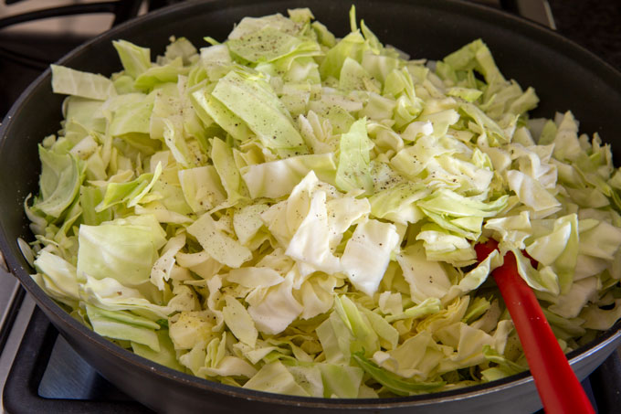 Adding the cabbage to the sautéed garlic and onions